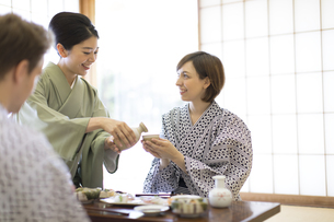 女将に日本酒を注いでもらう外国人観光客の写真素材 [FYI02973706]
