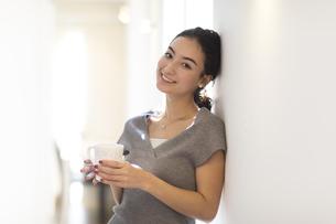 カップを持ちカメラ目線の女性の写真素材 [FYI02973707]