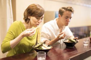 ラーメンを食べる男女の外国人観光客の写真素材 [FYI02973714]