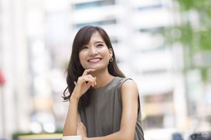 オープンカフェで顎に手をあて上を見上げる女性の写真素材 [FYI02973715]