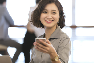 スマートフォンを持ち横を向くビジネス女性の写真素材 [FYI02973724]
