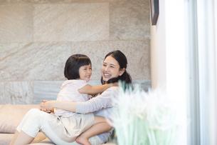 ソファーで戯れる母親と娘の写真素材 [FYI02973727]