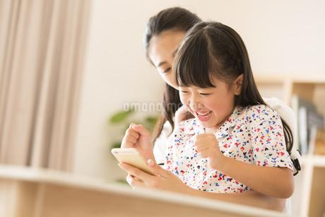 スマートフォンを見て楽しむ親子の写真素材 [FYI02973731]