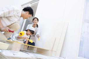 ベニヤ板にペンキを塗る家族の写真素材 [FYI02973741]