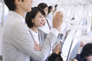 電車で男性と会話をするビジネス女性の写真素材 [FYI02973742]
