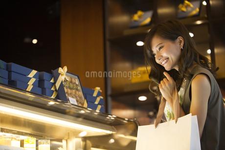 ショーウィンドウのケーキを選ぶ女性の写真素材 [FYI02973743]
