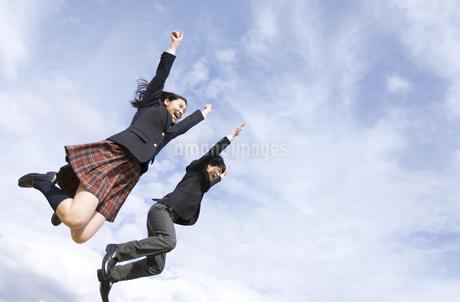 青空をバックにジャンプをする高校生たちの写真素材 [FYI02973769]