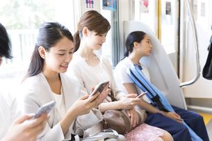電車の座席に座りスマホを操作するビジネス女性の写真素材 [FYI02973775]