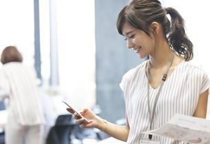 スマホを操作するビジネス女性の写真素材 [FYI02973791]