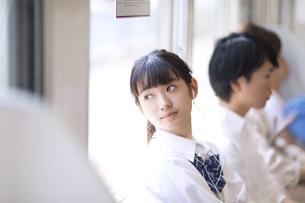 電車で音楽を聴きながら外の景色を見つめる女子高校生の写真素材 [FYI02973798]