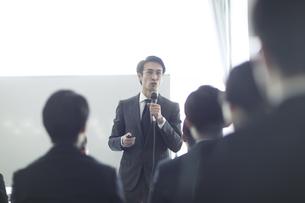 マイクを手に講義をするビジネス男性の写真素材 [FYI02973802]