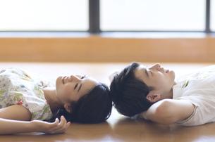 寝転がり頭をくっつける男女の写真素材 [FYI02973813]