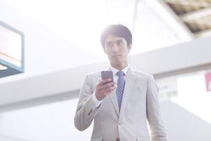 駅でスマホを持ちながら周りを見るビジネス男性の写真素材 [FYI02973820]