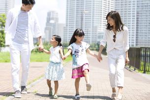 手をつないで遊歩道を歩く家族の写真素材 [FYI02973824]