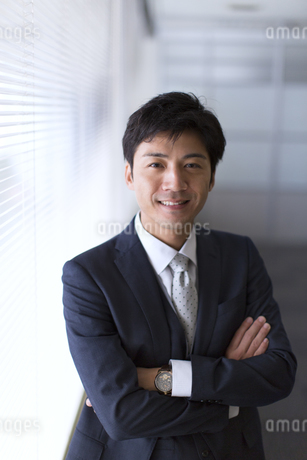オフィスの窓際で微笑むビジネス男性の写真素材 [FYI02973828]