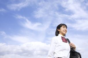 青空をバックに立つ女子高校生の写真素材 [FYI02973829]