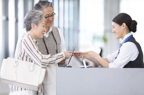 空港カウンターで手続きをするシニア夫婦の写真素材 [FYI02973845]