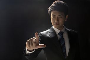 指を指すポーズをとるビジネス男性の写真素材 [FYI02973847]