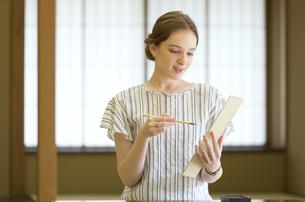 短冊に俳句を書く外国人女性の写真素材 [FYI02973849]