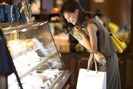 ショーウィンドウのケーキを選ぶ女性の写真素材 [FYI02973860]