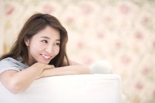 ソファに寄り掛かって微笑む女性のポートレートの写真素材 [FYI02973863]