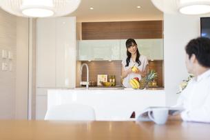 夫と会話をしながら料理をする妻の写真素材 [FYI02973866]