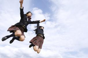 青空をバックにジャンプをする女子高校生たちの写真素材 [FYI02973873]