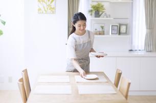 お皿をテーブルに置く女性の写真素材 [FYI02973877]