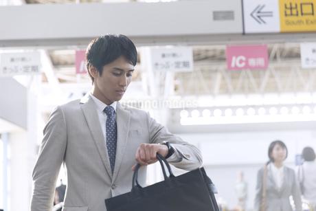 駅で時計を見るビジネス男性の写真素材 [FYI02973885]