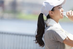 運動後にミネラルウォーターを飲む女性の横顔の写真素材 [FYI02973886]