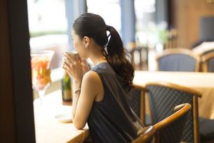 カフェでコーヒーを飲んでくつろぐ女性の後ろ姿の写真素材 [FYI02973888]