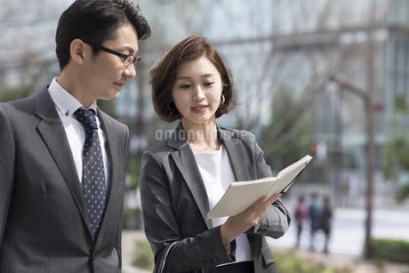 歩きながら打ち合わせをするビジネス男女の写真素材 [FYI02973889]