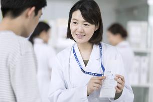 受付で薬の説明をする女性薬剤師の写真素材 [FYI02973892]