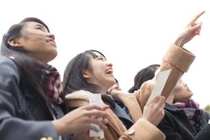 受験番号票を手に番号を確認している女子高校生たちの写真素材 [FYI02973895]