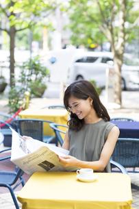 オープンカフェで新聞を読む女性の写真素材 [FYI02973896]