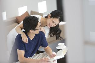 本を読む夫の背に抱きつく妻の写真素材 [FYI02973900]