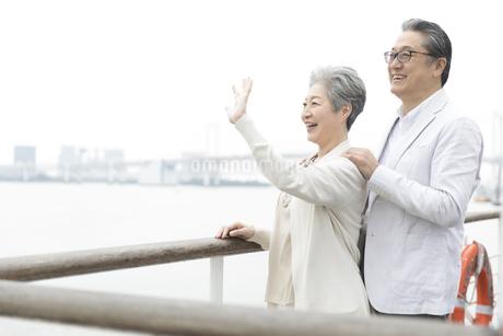 デッキで手を振るシニア夫婦の写真素材 [FYI02973905]