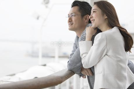 デッキで遠くを見る夫婦の写真素材 [FYI02973912]