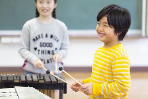 音楽室で木琴を叩く男の子と女の子の写真素材 [FYI02973915]