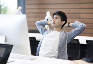 PCの前で伸びをするビジネス男性の写真素材 [FYI02973917]