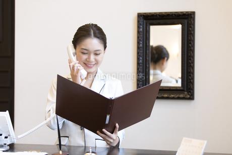 電話対応をするコンシェルジュの女性の写真素材 [FYI02973920]