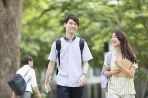 会話をしながら歩く学生の男女の写真素材 [FYI02973921]
