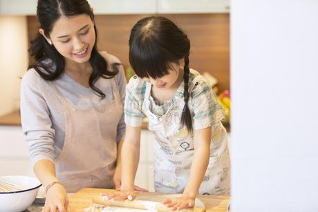 キッチンで料理を作る母親と娘の写真素材 [FYI02973922]