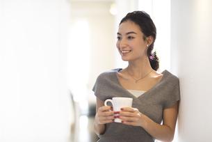 カップを持ち壁にもたれる女性の写真素材 [FYI02973924]