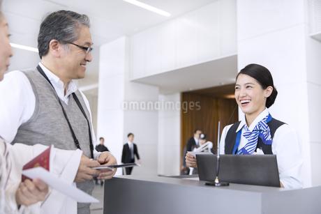 空港カウンターで対応する空港職員の女性の写真素材 [FYI02973928]