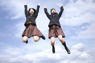 青空をバックにジャンプをする女子高校生たちの写真素材 [FYI02973929]