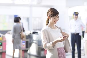 駅の改札付近でスマホを見るビジネス女性の写真素材 [FYI02973933]