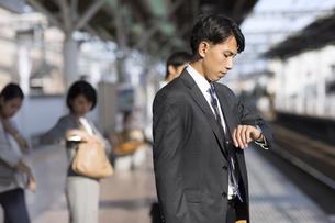 駅のホームで電車を待つビジネス男性の写真素材 [FYI02973934]