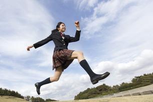青空をバックにジャンプをする女子高校生の写真素材 [FYI02973935]