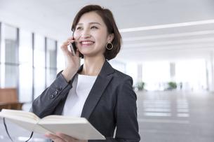 手帳を持ちスマートフォンで通話するビジネス女性の写真素材 [FYI02973936]